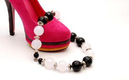 Necklace on pink female shoe Stock Image