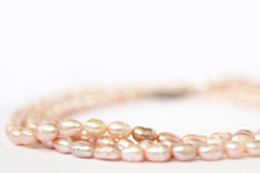 Necklace pink freshwater pearls. Necklace of pink freshwater pearls  on white background. Luxury wedding background. Photo of Macro shot of jewelry Royalty Free Stock Images