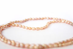 Necklace of pink freshwater pearls. On white background. Luxury wedding background. Photo of Macro shot of jewelry Stock Photography
