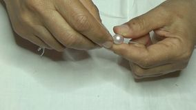 Necklace of Pink Pearls. Preparation of a pink pearl necklace. Binding hand stock video footage