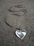 Necklace with quartz heart. Necklace with quartz heart attached to a black cord all laying upon black sand Royalty Free Stock Photography