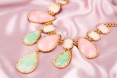 Necklace. Stylish necklace with colorful stones on pink fabric background Royalty Free Stock Images
