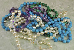 Necklaces of Gems. Malachite, turquoise, amethyst, pearl beads on a uniform greenish-gray fonefone Stock Images