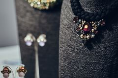 Necklaces with gemstones on a black jewelry bust in a store. Ostly necklaces with gemstones on a black jewelry bust in a store stock photography