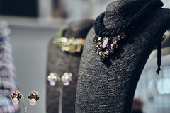 Necklaces with gemstones on a black jewelry bust in a store. Ostly necklaces with gemstones on a black jewelry bust in a store royalty free stock image