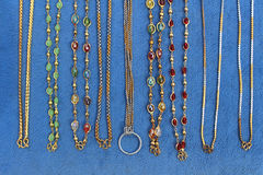 Necklaces gold on blue cloth. Close up necklaces gold on blue cloth Royalty Free Stock Images