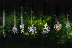 Necklaces hang elephant key heart green background dark.  royalty free stock photo