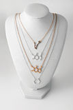 Necklaces in shape of molelule and constellation Pisces made of gold and silver on white stand. Luxury women accessories. Stock Image