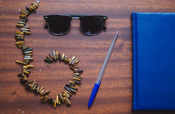 Necklase、玻璃、笔和笔记本 库存照片
