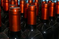 Necks of wine bottles with bright red foil closeup. Dusty necks of wine bottles with beautiful shiny bright red capsules foil closeup royalty free stock images