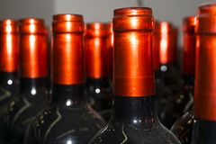 Necks of wine bottles with bright red foil closeup. Dusty necks of wine bottles with beautiful shiny bright red capsules foil closeup royalty free stock photography