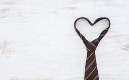Necktie in heart shape on grunge white wooden table background. Top view with copy space. Father& x27;s day background concept. Abstract accessories accessory royalty free stock photos