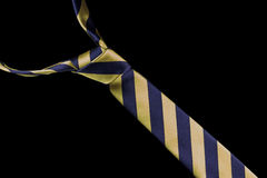 Necktie in silk with gold and blue stripes. One necktie isolated against a black background. Gold and blue stripes Stock Photos