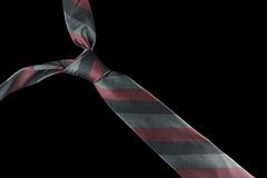 Necktie in silk with red and green stripes. One necktie isolated against a black background. Stripes in red and different shades of green Royalty Free Stock Photography
