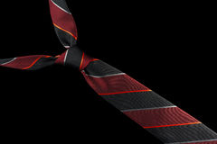 Necktie in silk with red, silver and black stripes. One necktie isolated against a black background. Stripes in red, silver and black Royalty Free Stock Image