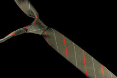 Necktie in silk with red, white and green stripes. One necktie isolated against a black background. Stripes in red, white and green Stock Photography