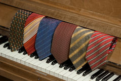 Neckties over a piano Stock Photos