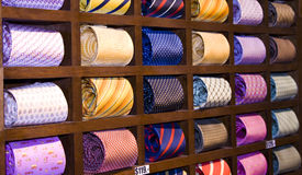 Neckties in a shelf. Many neckties displayed on a shelf in a store. Focus oat the second row, on the striped yellow tie Royalty Free Stock Photo