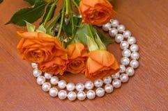 Neclace de la perla y rosas rojas Fotografía de archivo libre de regalías