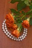 Neclace de la perla y rosas rojas Imagen de archivo libre de regalías