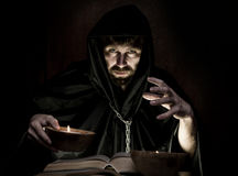 Necromancer casts spells from thick ancient book by candlelight on a dark background Royalty Free Stock Image