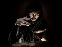 Necromancer casts spells from thick ancient book by candlelight on a dark background Royalty Free Stock Photos