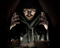Necromancer casts spells from thick ancient book by candlelight on a dark background.  Royalty Free Stock Images