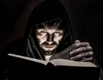 Necromancer casts spells from thick ancient book by candlelight on a dark background.  Stock Images