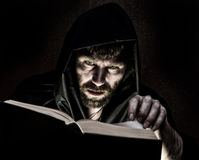 Necromancer casts spells from thick ancient book by candlelight on a dark background Stock Image