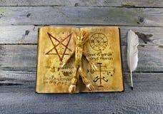 Necronomicon bok med voodoodockan Arkivbild
