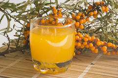 Nectar from berries of sea-buckthorn berries. The Image of a glass with juice against sea-buckthorn berries branch Stock Photo