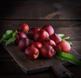 Nectarina madura vermelha dos pêssegos em uma placa de madeira marrom Fotos de Stock Royalty Free