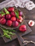 Nectarina madura vermelha dos pêssegos em uma placa do ferro Fotografia de Stock Royalty Free
