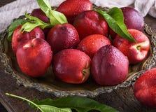 Nectarina madura vermelha dos pêssegos em uma placa do ferro Foto de Stock