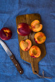 Nectarina maduras frescas, partido ao meio, inteiras na placa de corte de madeira, faca, no pano de tabela azul, vista superior,  Fotos de Stock