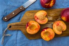 Nectarina maduras frescas, partido ao meio, inteiras na placa de corte de madeira, faca, no pano de tabela azul, vista superior,  Fotos de Stock Royalty Free