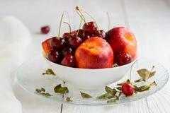 Nectarinas, cerezas con las gotitas de agua en el cuenco blanco imagen de archivo