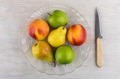 Nectarinas, peras, manzanas en plato transparente y cuchillo de cocina Fotos de archivo libres de regalías