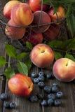 Nectarinas y melocotones en la tabla de madera en un estilo rústico Fotos de archivo