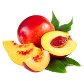 Nectarine. Fresh juicy nectarine with green leaves on a white stock photo