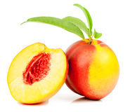 Nectarine. Red and yellow whole and half  with green leaves   over white background Stock Photography
