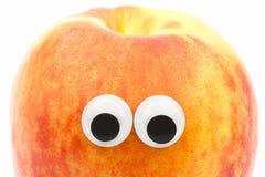 Nectarine avec les yeux écarquillés sur le fond blanc Image stock