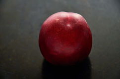 Nectarine fruit on a dark background in the center closeup Royalty Free Stock Images