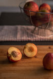 Nectarine halves on chopping board with apples in the background. Stock Photos