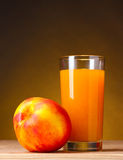 Nectarine and juice glass Stock Photos