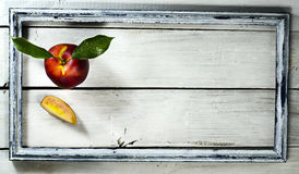 Nectarine in old frame on a white wooden background. Nectarine with leaf in old frame on a white wooden background stock photos