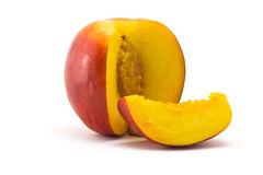Nectarine. One ripe juicy nectarine and cut portion on a white background stock photos
