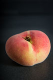 Nectarine peach, flat peach, still life, vertical with dark background Royalty Free Stock Photo