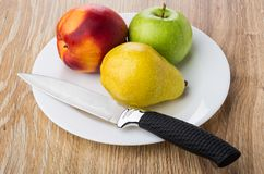 Nectarine, pear, apple and kitchen knife in plate on table. Nectarine, pear, apple and kitchen knife in white plate on wooden table Stock Photos