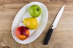 Nectarine, pear and apple in dish, kitchen knife on table. Nectarine, pear and apple in white dish, kitchen knife on wooden table. Top view Royalty Free Stock Photography
